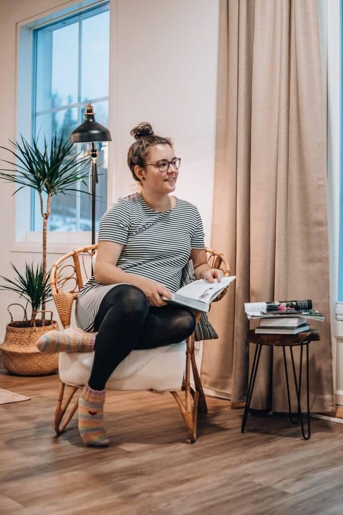 Maria istuu korituolissa kirja kädessään ja katsoo ulos hymyillen