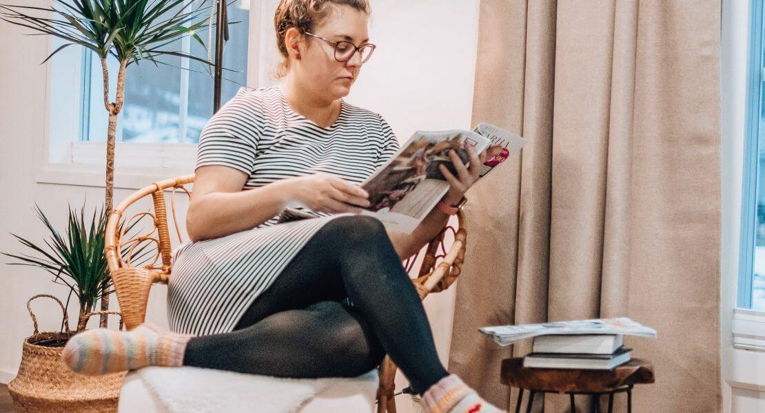 Maria istuu korituolissa ja lukee lehteä