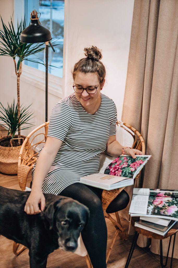 Maria istuu korituolissa kirja kädessään ja rapsuttaa vierelle tullutta koiraa