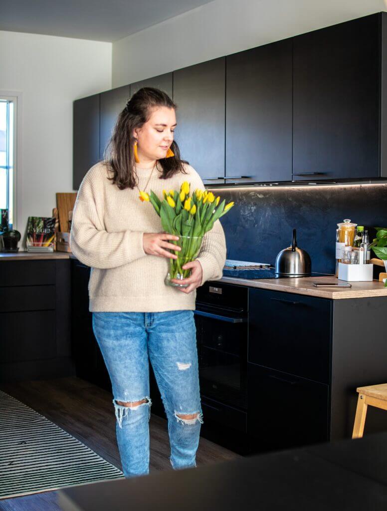 Maria keittiössä sylissäään kimppu tulppaaneja